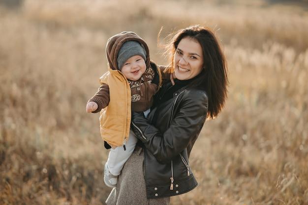 Gelukkige moeder en zoon jong meisje lacht knuffels haar baby