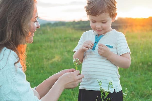 Gelukkige moeder en zoon op aard op zonsondergang