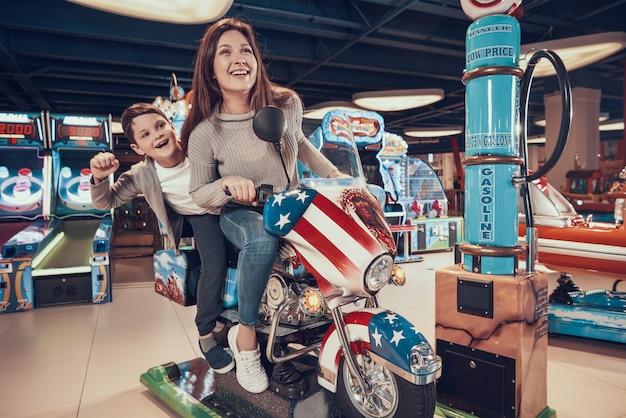 Gelukkige moeder en zoon op speelgoed motorfiets.
