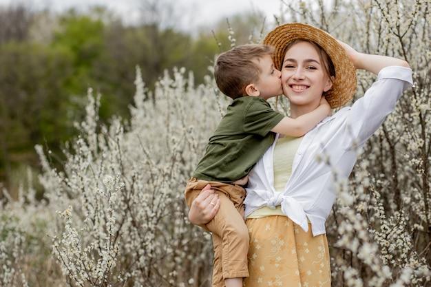 Gelukkige moeder en zoon samen plezier. moeder knuffelt zachtjes haar zoon. op de achtergrond bloeien witte bloemen. moederdag
