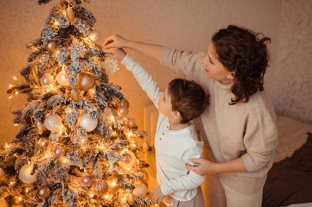 Gelukkige moeder en zoon thuis in de slaapkamer dichtbij de kerstboom