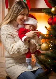 Gelukkige moeder en zoontje in kerstmankostuum die de kerstboom versieren