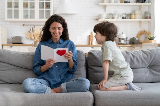 Gelukkige moeder geniet van het lezen van een ansichtkaartcadeau van een klein zoonkind op moederdagverjaardag of valentijnsdag
