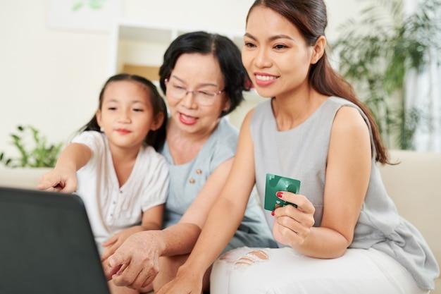 Gelukkige moeder, grootmoeder en klein meisje die samen online winkelen, eten of kleding bestellen en met creditcard betalen