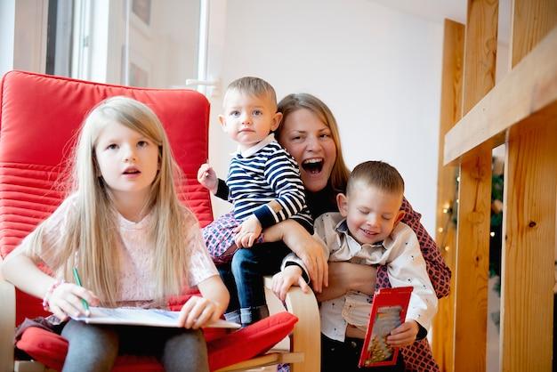Gelukkige moeder heeft het naar haar zin met haar drie kinderen in het ouderlijk huis, kinderen tekenen met potloden
