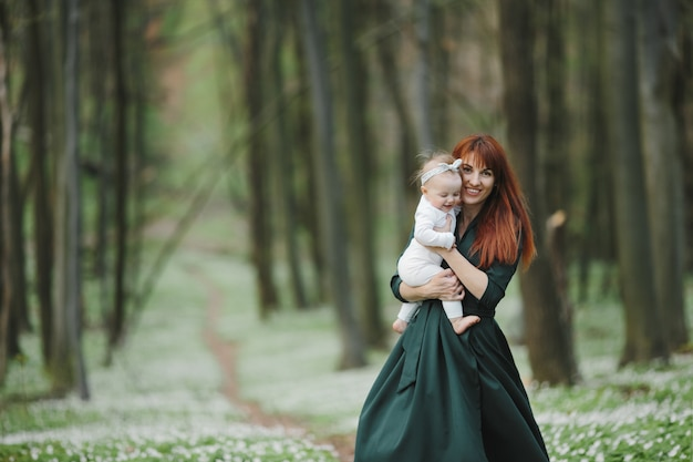 Gelukkige moeder houdt haar dochtertje stevig vast