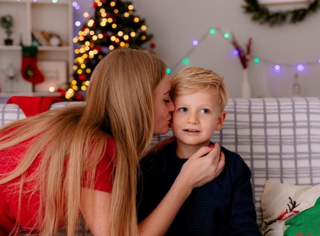 Gelukkige moeder in rode jurk kuste haar kleine kind zittend op een bank in een ingerichte kamer met kerstboom op de achtergrond