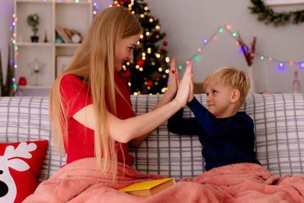 Gelukkige moeder in rode jurk met haar kleine kind onder deken met een boek met plezier high five geven in een ingerichte kamer met kerstboom in de muur