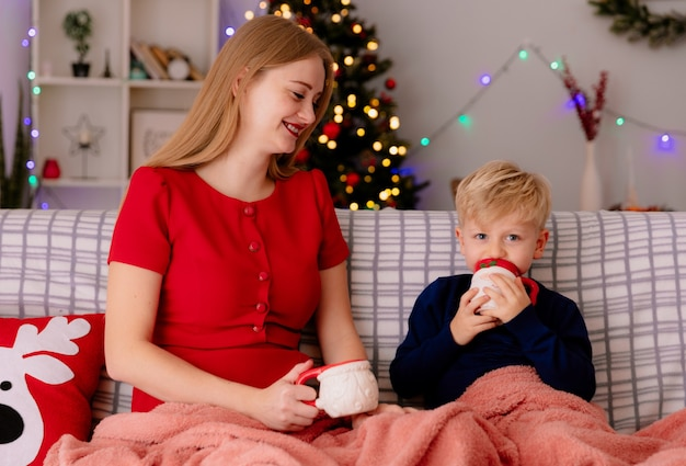 Gelukkige moeder in rode jurk met haar kleine kind zittend op een bank onder deken die thee drinkt uit mokken in een ingerichte kamer met kerstboom in de muur