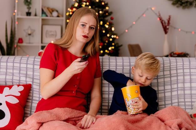 Gelukkige moeder in rode jurk met haar kleine kind zittend op een bank onder deken met emmer popcorn samen tv kijken in een ingerichte kamer met kerstboom in de muur