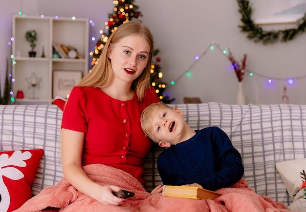 Gelukkige moeder in rode jurk met tv-afstandsbediening en haar kleine kind onder deken met een boek in een versierde kamer met kerstboom in de muur