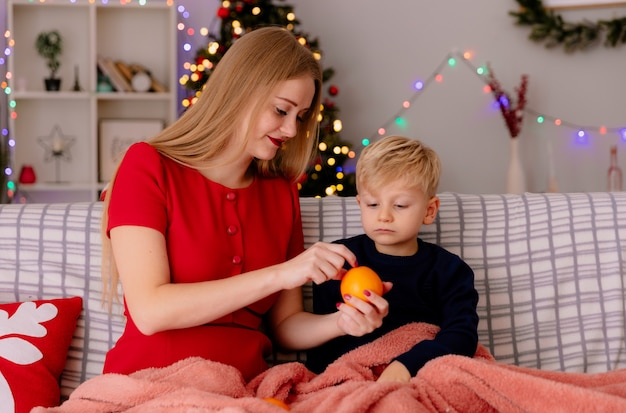 Gelukkige moeder in rode jurk oranje geven aan haar kleine kind zittend op een bank onder deken in een ingerichte kamer met kerstboom op de achtergrond