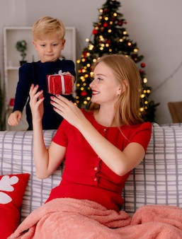 Gelukkige moeder in rode jurk zittend op een bank glimlachend terwijl haar kleine kind achter haar staat en een geschenk geeft aan zijn moeder in een versierde kamer met kerstboom op de achtergrond