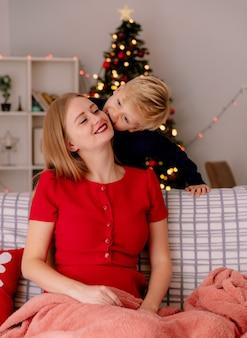 Gelukkige moeder in rode jurk zittend op een bank glimlachend terwijl haar kleine kind achter zijn moeder staat te kussen in een ingerichte kamer met kerstboom in de muur