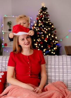 Gelukkige moeder in rode jurk zittend op een bank glimlachend terwijl haar kleine kind staande achter kerstmuts op zijn moeders hoofd zet in een ingerichte kamer met kerstboom in de muur