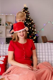 Gelukkige moeder in rode jurk zittend op een bank lachend terwijl haar kleine kind