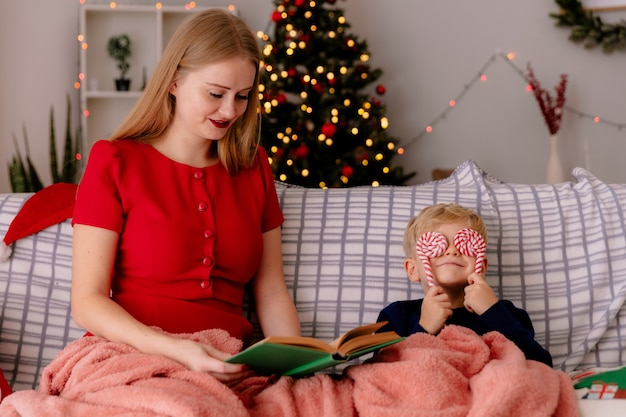 Gelukkige moeder in rode jurk zittend op een bank met haar kleine kind onder deken leesboek in een versierde kamer met kerstboom in de muur