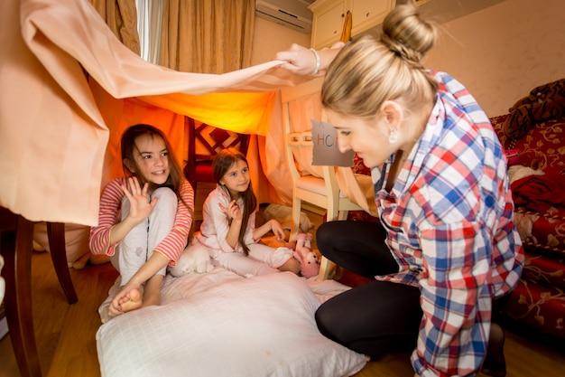 Gelukkige moeder kijkt naar twee dochters die spelen in een zelfgemaakt huis in de slaapkamer