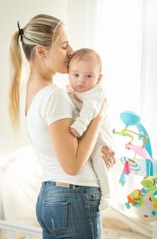 Gelukkige moeder knuffelt haar 3 maanden oude baby bij groot raam in bedrrom