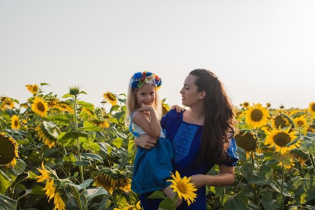 Gelukkige moeder knuffelt haar dochter in een zonnebloemveld