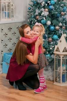 Gelukkige moeder knuffelt haar schattige blonde dochter in de buurt van nieuwjaarsboom