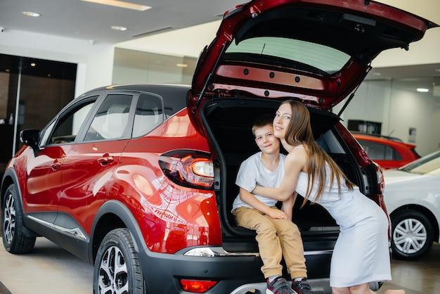 Gelukkige moeder knuffelt haar zoon nadat ze een nieuwe auto heeft gekocht bij een autodealer
