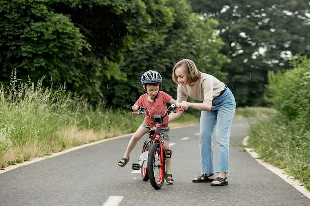 Gelukkige moeder leert zoontje fietsen op het fietspad