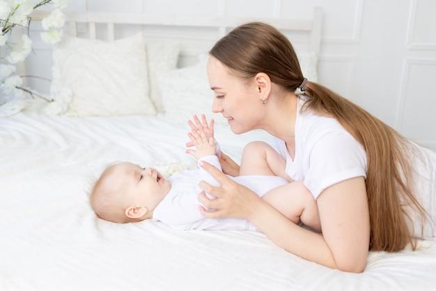 Gelukkige moeder met baby die zachtjes speelt en knuffelt op het bed thuis
