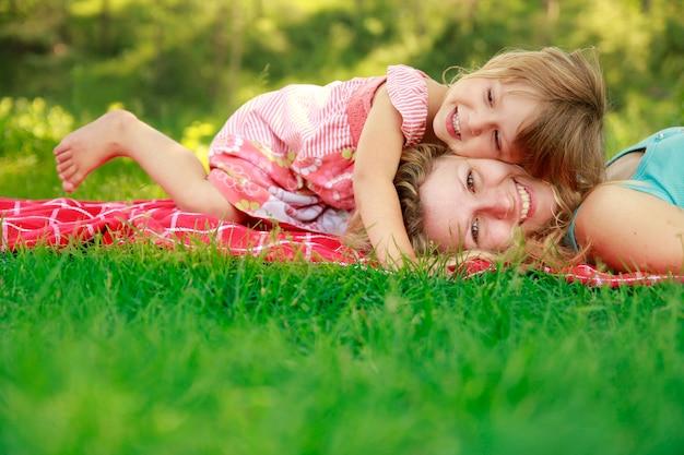 Gelukkige moeder met baby in de natuur liggend op het gras in het park