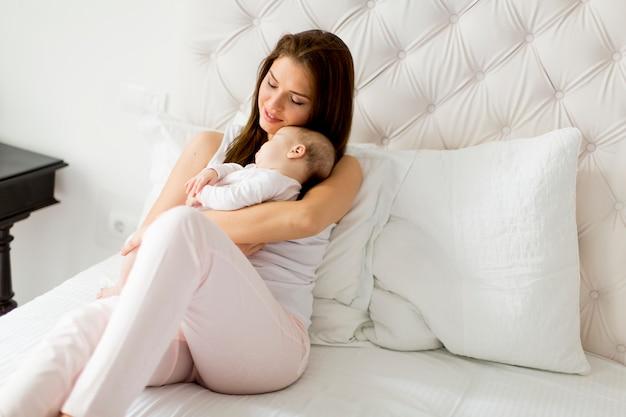 Gelukkige moeder met baby op bed