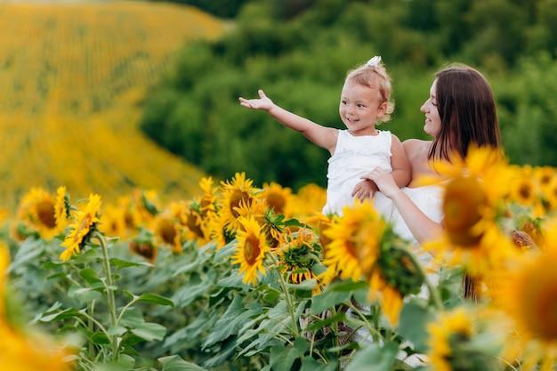 Gelukkige moeder met de dochter in het veld met zonnebloemen. moeder en babymeisje plezier buitenshuis. familie concept. moederdag, baby's dag. zomervakantie