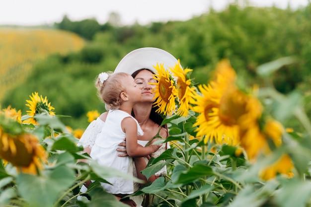 Gelukkige moeder met de dochter in het veld met zonnebloemen. moeder en babymeisje plezier buitenshuis. familie concept. selectieve aandacht