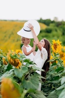 Gelukkige moeder met de dochter in het veld met zonnebloemen. moeder en babymeisje plezier buitenshuis. familie concept.