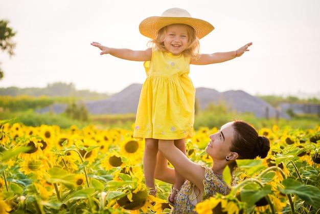 Gelukkige moeder met de dochter in het veld met zonnebloemen