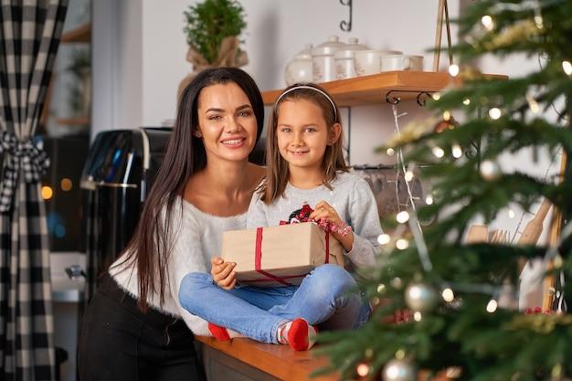 Gelukkige moeder met dochtertje die een kerstcadeautje kreeg van de kerstman