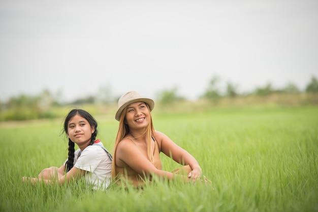 Gelukkige moeder met dochterzitting op het park van het grasgebied