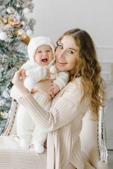 Gelukkige moeder met een klein kind naast de kerstboom