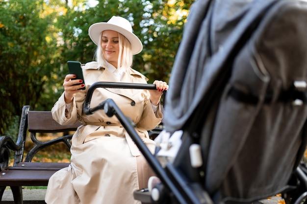 Gelukkige moeder met een smartphone in handen