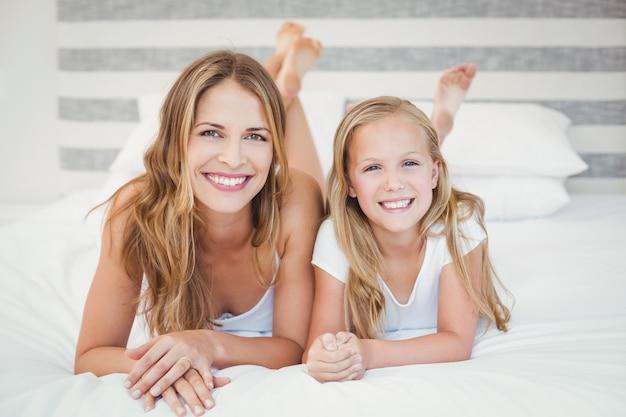 Gelukkige moeder met haar dochter die op bed ontspant