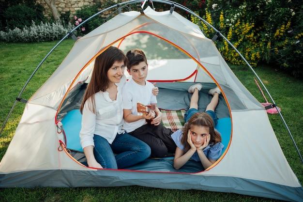Gelukkige moeder met haar dochter en zoon in tent op gras bij park