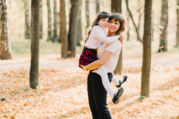 Gelukkige moeder met haar dochter in haar armen glimlachen