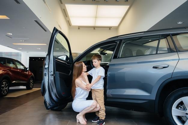 Gelukkige moeder met haar jonge zoon kiest een nieuwe auto bij een autodealer