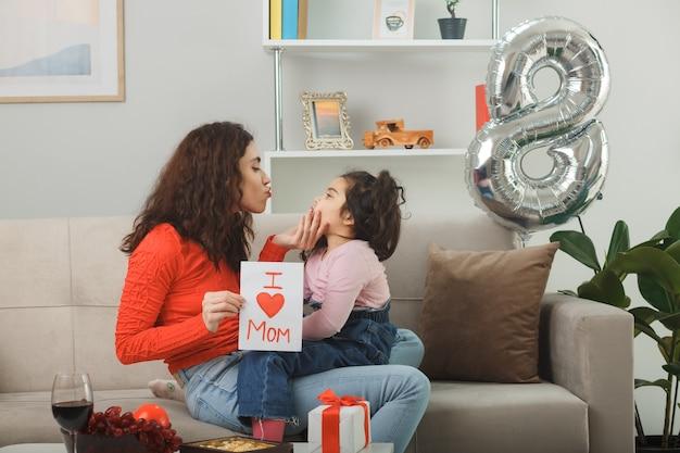 Gelukkige moeder met haar kleine kind dochter zittend op een bank met wenskaart glimlachend vrolijk in lichte woonkamer vieren internationale vrouwendag 8 maart