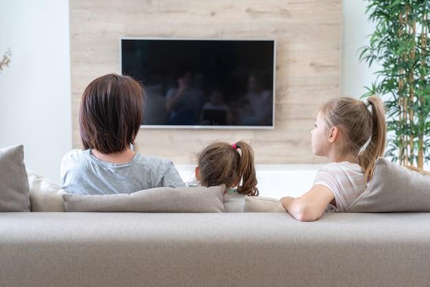 Gelukkige moeder met haar twee schattige dochters thuis tv-kijken. ontspannen op de coach en gelukkige familie.