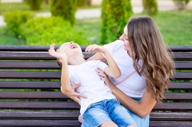 Gelukkige moeder met haar zoontje in het park op een bankje in de zomer veel plezier met knuffelen, lachen en spelen