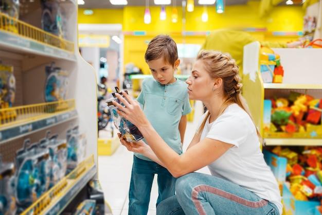 Gelukkige moeder met haar zoontje speelgoed in kinderwinkel kiezen