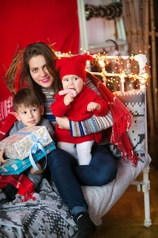 Gelukkige moeder met kinderen, plezier maken, knuffelen in het interieur dat is ingericht voor het nieuwe jaar