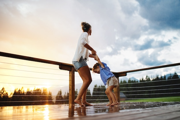 Gelukkige moeder met kleine dochter die in de regen speelt op het terras van een houten hutvakantie in de natuur