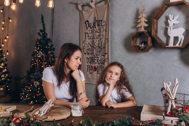 Gelukkige moeder met krullende dochter in gezellige kerst keuken, familie vakantie huis vrije tijd samen