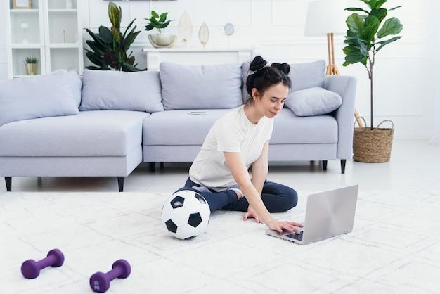 Gelukkige moeder op de vloer thuis met kinderen en kijk naar grappige cartoon op laptop.